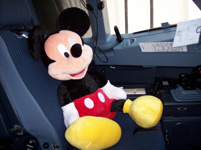 Mickey Mouse sitting in the pilots seat on the airplane.