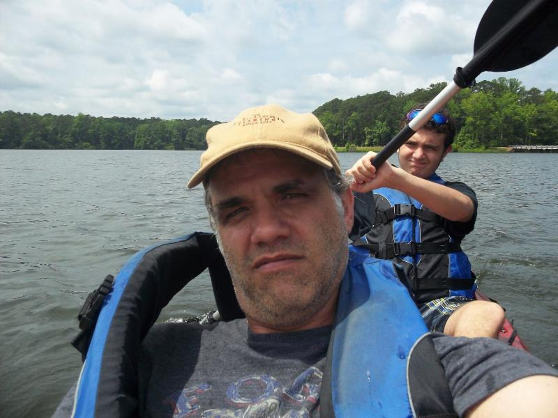 Matt kayaking with his son Max.  Matt is in the front and Max in the back holding the paddle.