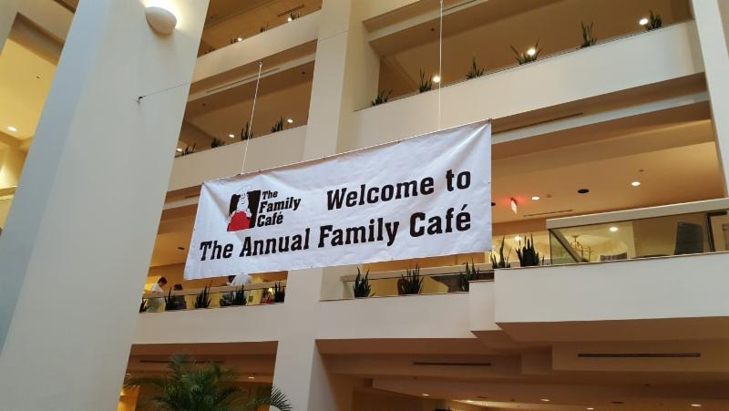 A white banner hangs from the ceiling that says Welcome to The Annual Family Café