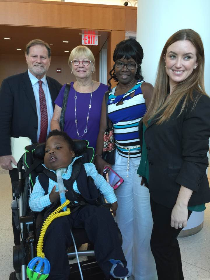 Five people smile at the camera after D. Davis was adopted by his grandma
