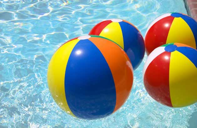 Colorful beach balls floating in a pool