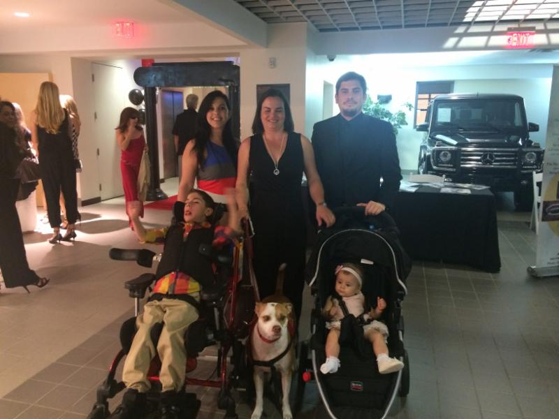 Our client, Monica Albonaga, and her family pose with Disability Independence Group staff at the Lucky 13 Casino Night by the Pets Trust