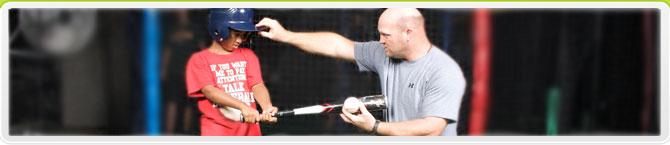 A baseball coach teaches the player how to swing a bat.