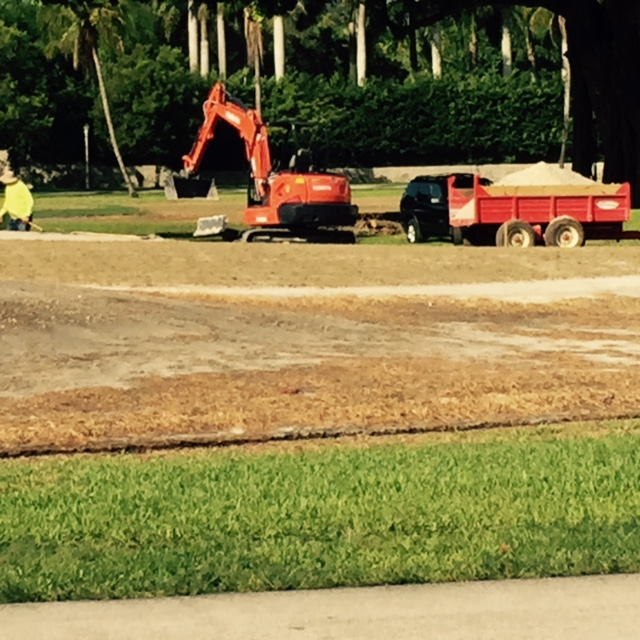 A tractor taking out clumps of grass from the perimeter of the city golf course