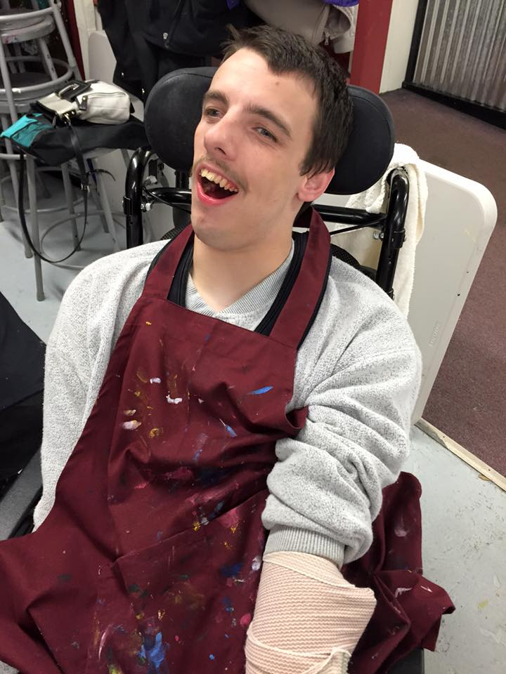 Nick, smiling and wearing an apron covered with paint