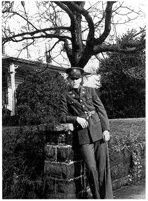 bob in uniform leaning on a stone wall with trees in the background