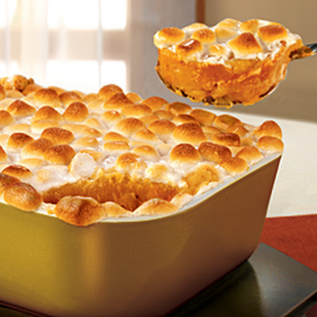 casserole with marshmallow topping being scooped out with a large spoon