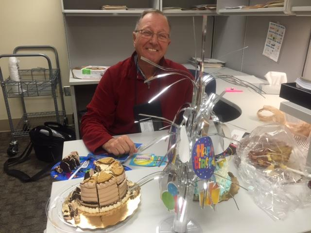 Lester Langer sitting and smiling with a birthday cake and presents in front of him celebrating his 70th birthday.