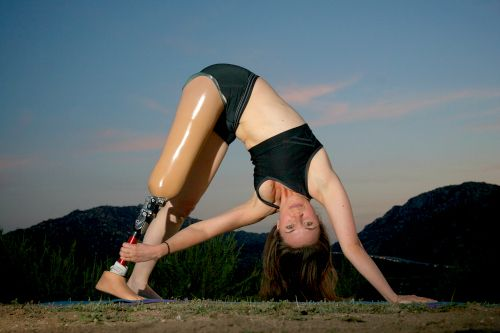 A lady with a prosthetic leg in a yoga position.