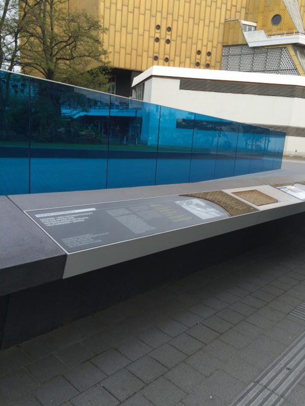 Part of the memorial is shown. The majority of the long blue glass wall is visible with a long lower grey counter running parallel to the wall and directly in front of it. The counter has written text and multimedia screens on it. The picture has been take