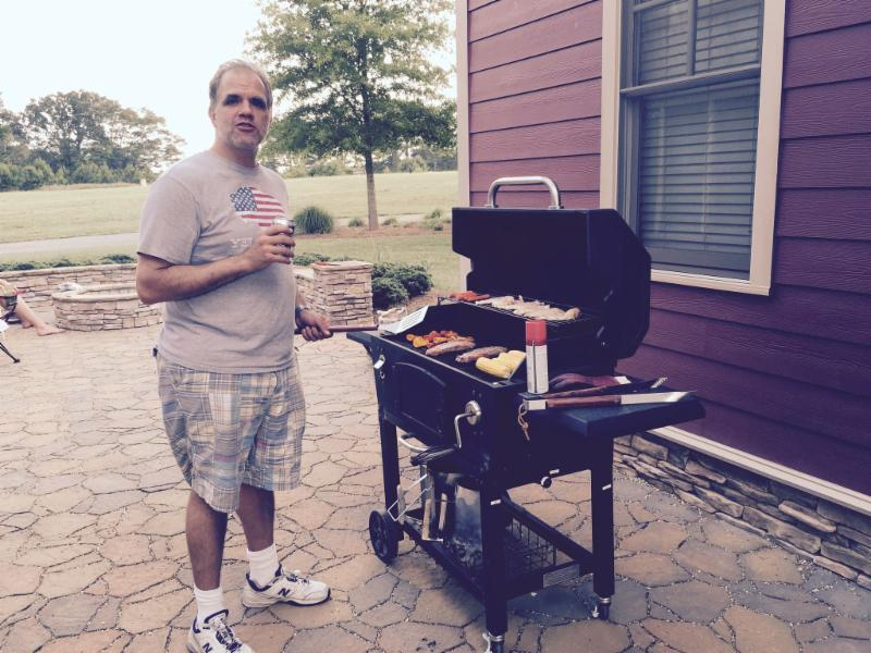 Matt standing in front his BBQ cooking dinner.