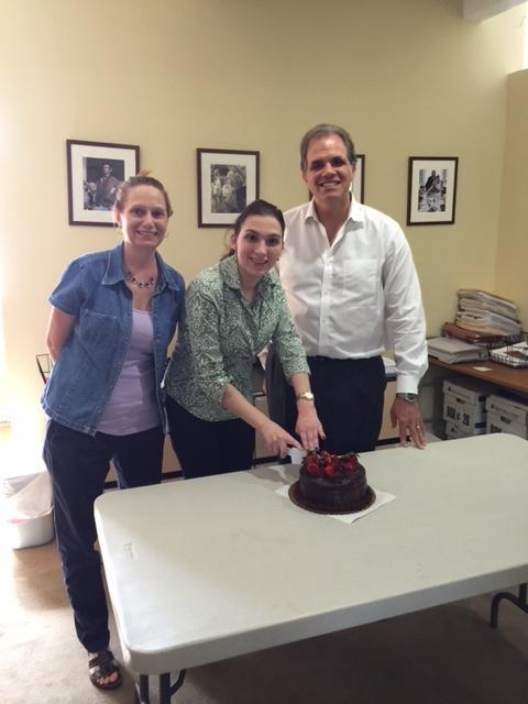 Debbie, Danielle, and Matt cutting a cake to say goodbye to Danielle.