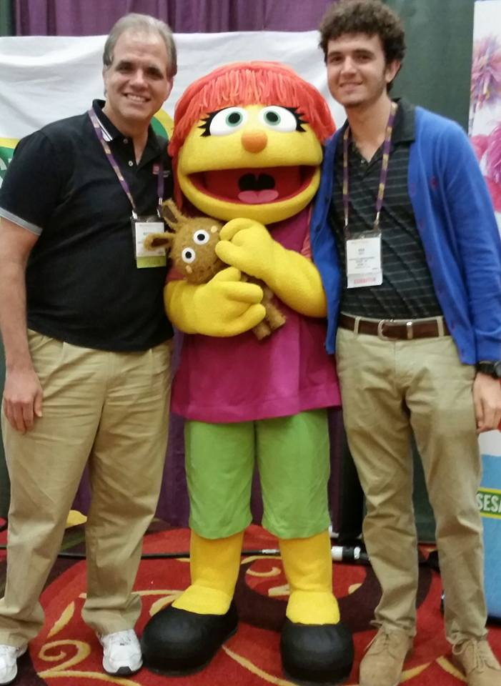 Matt and Max standing with Julia the new character on Sesame Street.