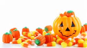 picture of Halloween candy pumpkins and candy corn with a jack-o-lantern in the right corner