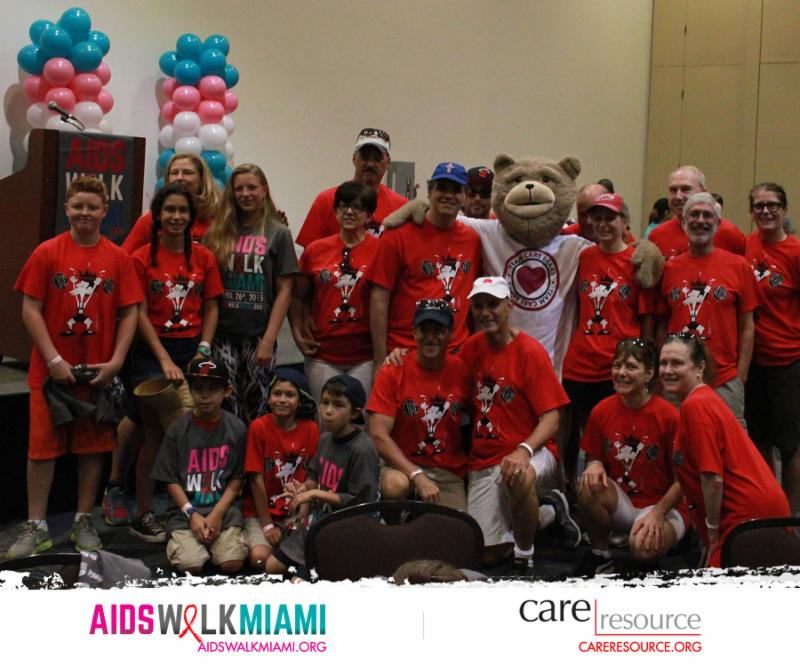 Matt and Debbie Dietz pose with a group of participants and the AIDS Walk mascot, a life-sized teddy bear