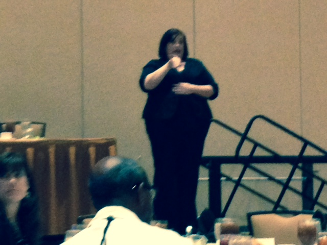 Interpreter signing in ASL at FL Bar luncheon.