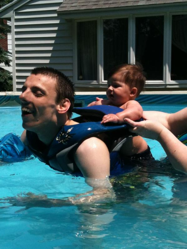 Nick swimming with a little baby on his back.