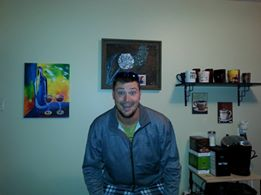 Adam smiling with the painting hung on the wall behind him