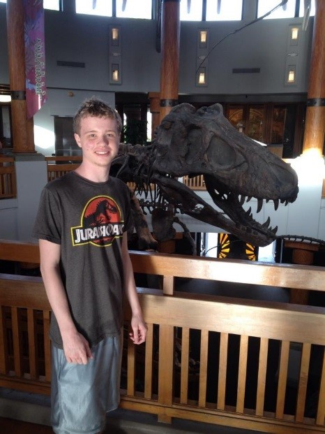 Nik S. wearing a jurasic park shirt and standing in front of the bones of a dinosaur head.