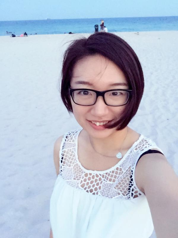 Picture of Hui Yu smiling at the beach with the ocean in the background