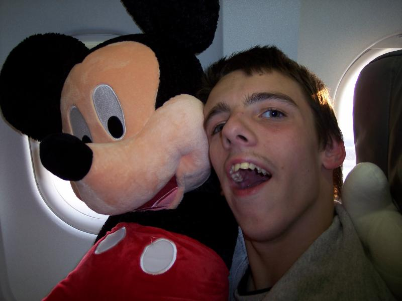 Nick smiling with Mickey Mouse on the airplane.