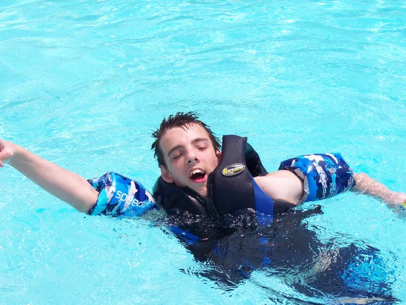 Nick swimming in the pool with his water wings and life jacket.