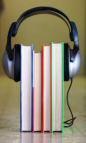 Four books surrounded by a pair of earphones.
