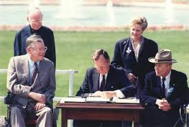 President sitting a table signed the ADA into law with four people surrounding him.