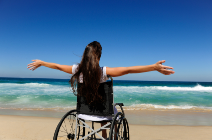 Girl in wheelchair on the beach with her arms outstretched toward the waves