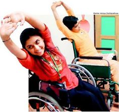 Two women in wheelchairs stretching their arms.