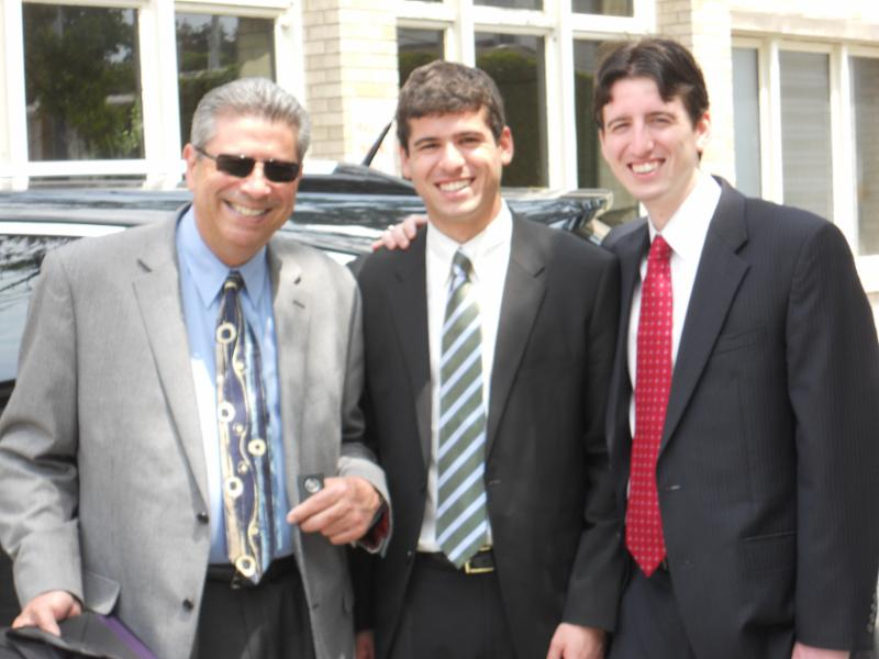 Mr. Reyes and his two sons standing together outside in front of a car.