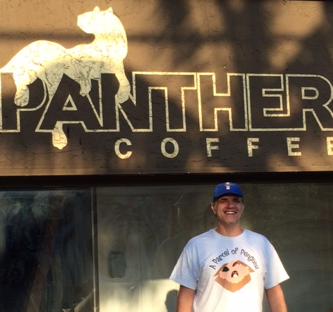 Matt standing outside of Panther Coffee wearing his penguin shirt.