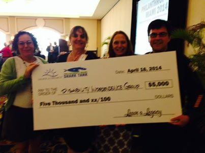 Associates of DIG holding up an oversided check from the Shark Tank Prize
