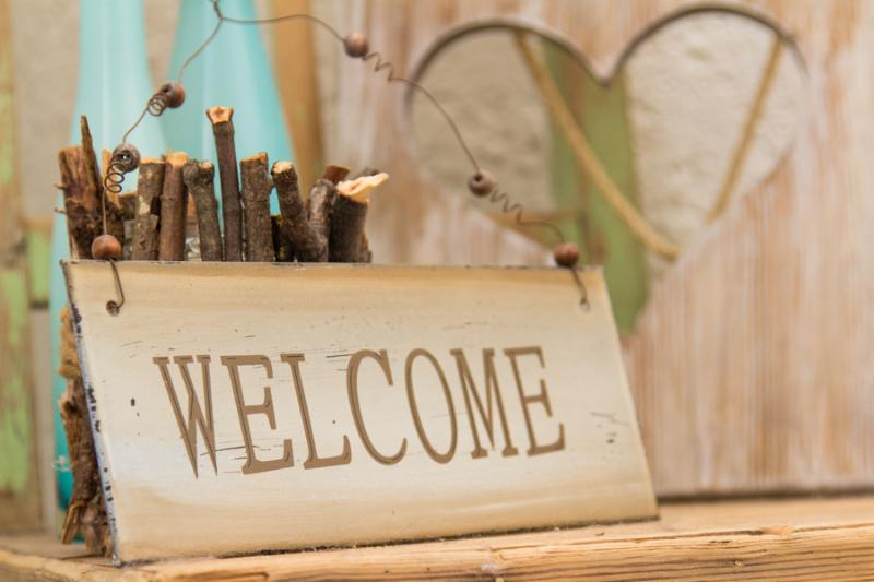 Rustic wooden WELCOME sign standing on a wooden shelf in front of a wood panel with a cut out heart