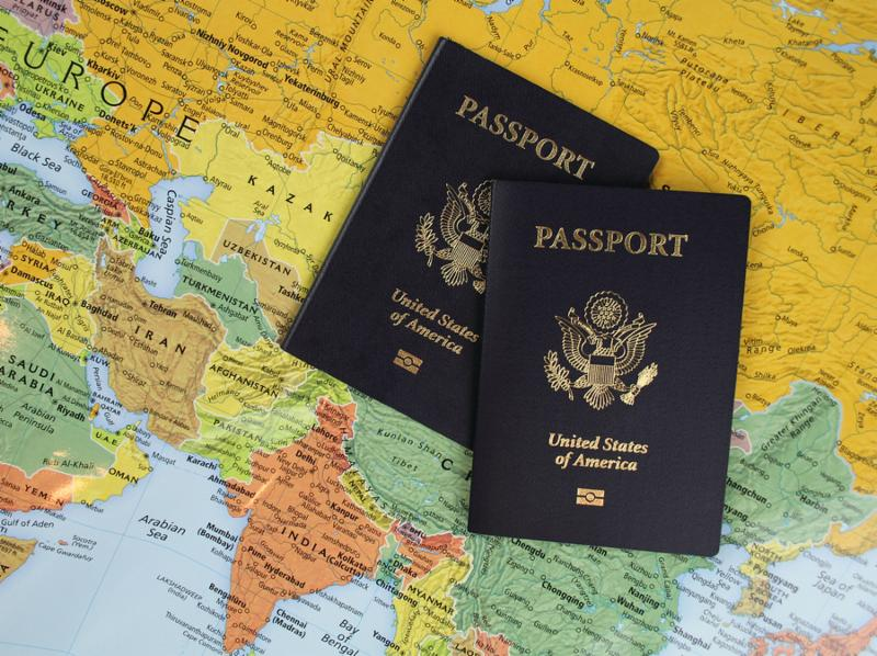Two US passports with a world map background