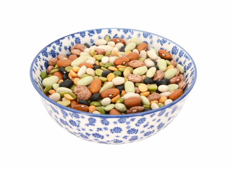 Mixed dried beans - black turtle beans flageolet beans pinto beans brown beans haricot beans and split peas - in a blue and white porcelain bowl with a floral design isolated on a white background