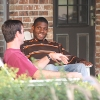 Two teens chat on the porch