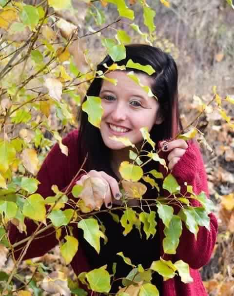 Photo of Kirsten peering through leaves of a tree