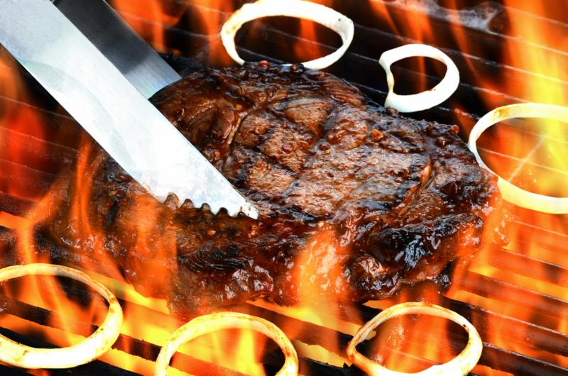 Delicious juicy rib eye steak on a barbecue grill with flames