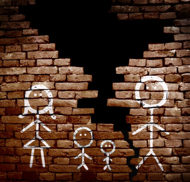 Family of stick figures on broken brick wall -- divorce or separation concept