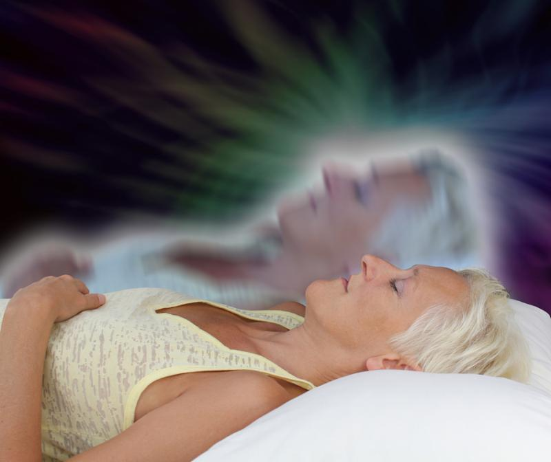 Female lying supine with eyes closed experiencing astral projection on dark background showing soul leaving body