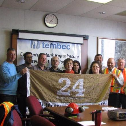 Group of newsprint workers holding gold flag