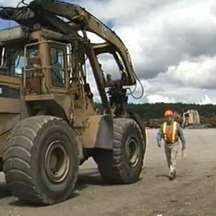 worker standing beside large truck loader