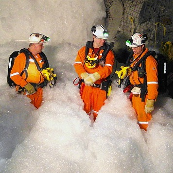 Videographer filming Alan, Paul and Mike in a sea of foam fire retardant