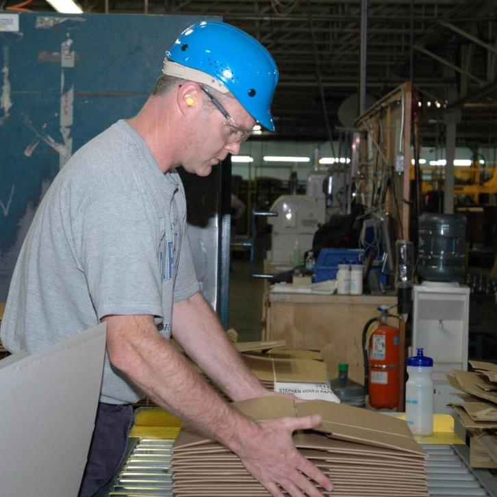 Worker stacking corrugated boxes