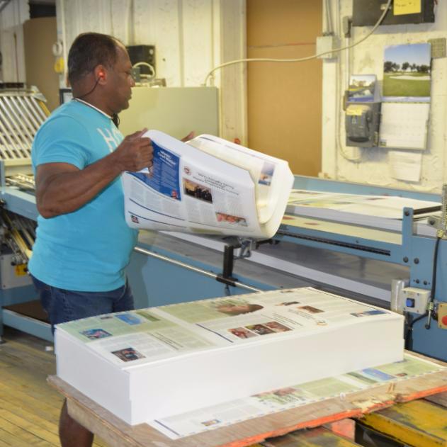 Printing press worker lifting stacks of paper