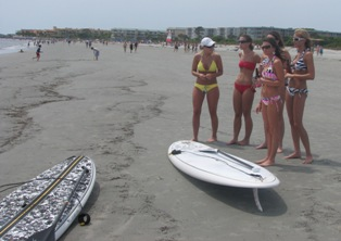 girls look at SUPs on East Beach at St Simons