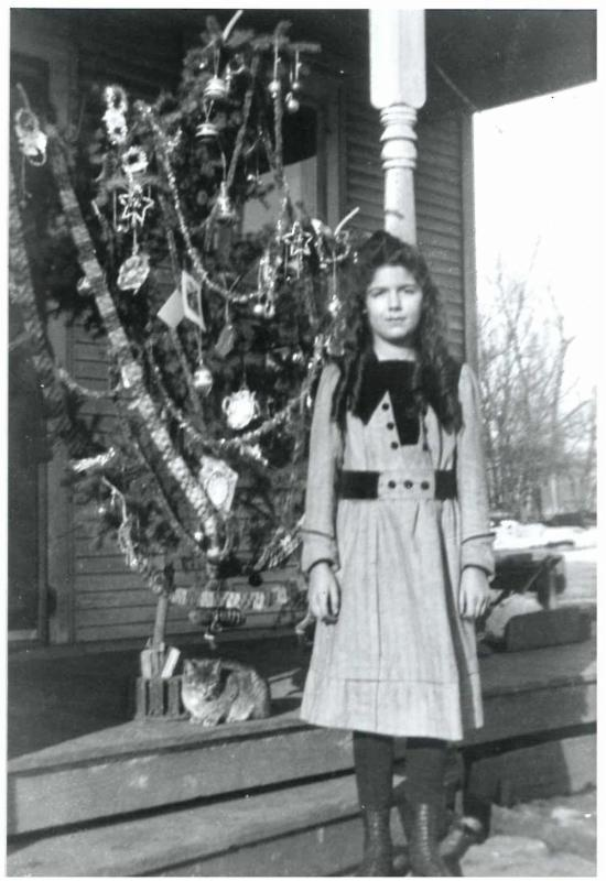 Merry Christmas from Schumacher Farm Park. This photo shows a young Marcella Schumacher posing with her cat and the Christmas tree circa 1920. Marcella is all dressed up so it's likely that this photo was taken on Christmas morning before church. They mus
