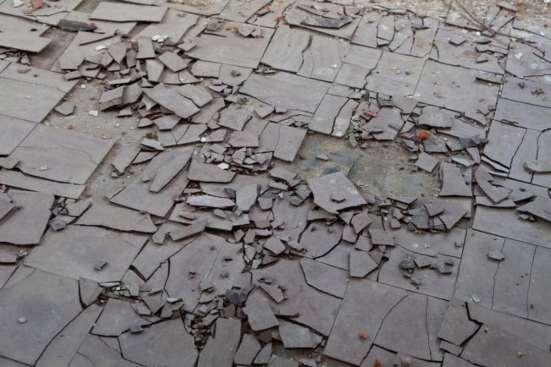 Old and broken asbestos floor tiles in an abandoned house