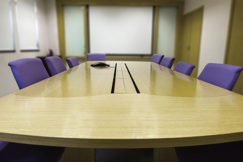 Meeting room with wooden table armchairs and white board. Office interior